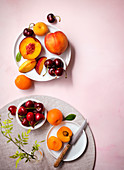 Table setting with summer fruits (nectarines, peaches, cherries and apricots)