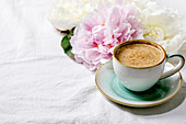 Cup of espresso coffee, pink and white peonies flowers with leaves over white cotton textile background