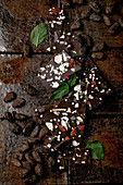 Handmade chopped dark chocolate with different superfood additives seeds and goji berries, cocoa beans and fresh mint