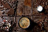 Tasse Kaffee, Milchkännchen, Bruchschokolade, Kakao- und Kaffeebohnen