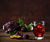Plum drink with ice cubes and fresh plums