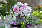 Kleiner Duftstrauß aus Flammenblumen, Rosen, Glockenblumen und Salbeiblättern in Stoffsäckchen auf Teller gestellt