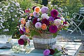 Üppiger Herbststrauß mit Dahlien, Rosen, Astern, Fencheldolden und Zieräpfeln im Korb