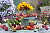 Selbstgebaute Etagere aus Haushaltsutensilien herbstlich dekoriert mit Äpfeln, Zieräpfeln, Hagebutten, Kastanien, Strohblumen und Strauß aus Sonnenblumen und Hagebutten