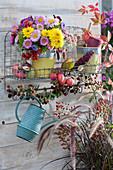 Herbststrauß aus Chrysanthemen, Sommerastern, Hagebutten, Fetthenne und Zieräpfeln auf Wandhängegestell, Topf mit Bindegarn, Gießkanne, Zieräpfel und Brombeerzweig