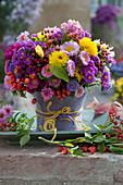 Herbststrauß aus Astern, Chrysanthemen, Sommerastern, Hagebutten und Zieräpfeln, Vase verkleidet mit Filz