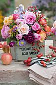 Herbststrauß aus Rosen, Astern und Hagebutten in Holzkiste