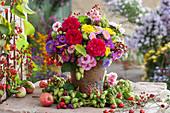 Herbststrauß mit Rosen, Astern, Chrysanthemen, Hopfen, Hagebutten und Sommeraster im Hopfenkranz