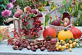 Zierapfel-Kränzchen an Korb mit frisch gepflückten Äpfeln, Kastanien, Kürbisse und wilder Wein als Deko