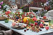 Herbstliche Tischdeko Hagebutten, Kürbis, Äpfeln, Kastanien, Schneebeeren, Haselnüssen und Weintrauben