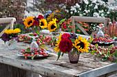Herbstliche Tischdeko mit Zieräpfeln, Sonnenblumen und Rosen