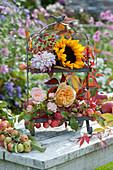 Metall-Etagere herbstlich dekoriert mit Sonnenblume, Rosenblüten, Dahlie, Zieräpfeln und Ranken vom wilden Wein