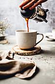 Mandel Latte zubereiten: Kaffee aus Cafetiere in Tasse gießen