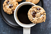 A tahini cookie with chocolate chunks put on the edge of a white ceramic mug filled with dark coffee on a black plate.