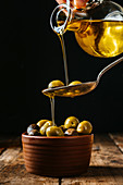 Pouring oil in spoon and ceramic bowl with olives placed on wooden table in kitchen