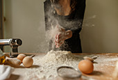 Unrecognizable female in black outfit clapping hands with flour while preparing dough on table with kitchen devices and eggs at home