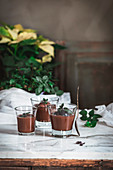 Still-life shoot of chocolate and mint mousse served inside glasses, placed on marble table