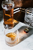 Whiskey in glass and bottle arranged on marble table in bar