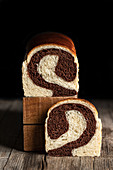 Homemade bread with chocolate and banana flavor placed on wooden table in kitchen on black background