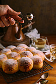 Crop anonymous chef sifting icing sugar using small metal sieve while decorating tasty golden buns near cups with green tea bags on table