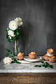 Still life of tasty yogurt cupcakes on round plates in arrangement with green leaves and aromatic white roses in glass vase