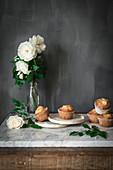 Joghurt-Cupcakes und weisse Rosen in Glasvase