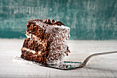 Chocolate cake slice with cream and coconut placed against shabby background