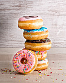 Stack of yummy sweet assorted donuts with colorful frosting and sprinkles placed on wooden background