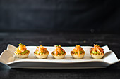 Tartlets with fish and guacamole arranged in row on white ceramic plate in restaurant
