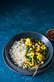Vegan indian cauliflower and cashewnut curry with spinach and rice