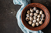 Quail eggs in a clay bowl with blue cheesecloth