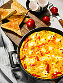 Breakfast eggs with peppers and feta cheese in a cast iron pan