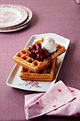 Waffles with sour cherries and whipped cream