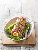 Meatloaf with egg filling and bacon coating on spring vegetables