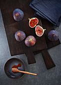 Fresh figs on a dark cutting board with a honey dipper