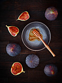 Fresh figs and a honey dipper on a dark wooden background