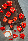 Tomatoes on a dark cutting board with coarse sea salt