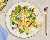 Frisée salad with wild flowers, rocket and rosemary chips
