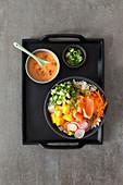 Poke bowl with smoked salmon, mango and radishes
