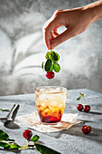 Iced cherry mocktail with hand holding cherry