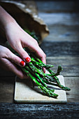 Women's hands put green asparagus on a cutting board