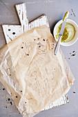 Küchenbrett, Pergamentpapier und Avocadocreme