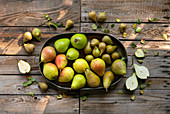 A composition of different kinds of pears on a wooden table top in the garden.