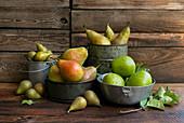 Verschiedene Birnensorten in Vintage-Gefäßen auf Holztisch
