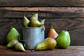 A composition of different kinds of pears on a wooden table in the garden