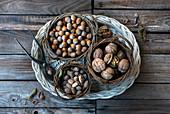 Verschiedene Nüsse in Weidenkörben auf Weidentablett