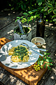 Spaghetti with lovage pesto on an outdoor table