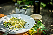 Spaghetti with lovage pesto on a table in the garden