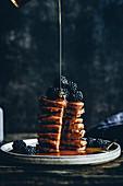 Ahornsirup fließt auf Kürbis-Pancakes mit Brombeeren