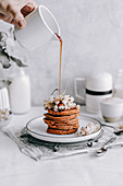 Pumpkin pancakes decorated with white currants topped with maple syrup